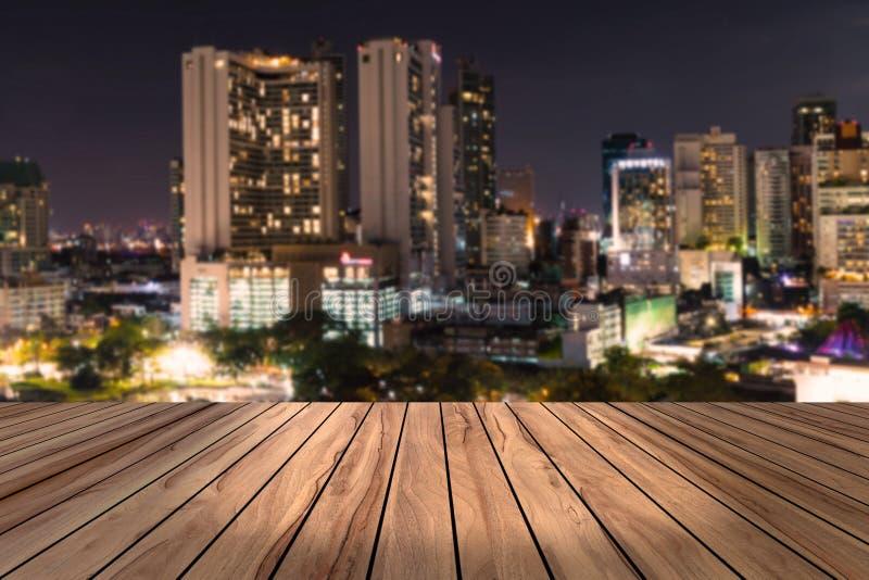 Τοπ ξύλινο γραφείο με το αστικό υπόβαθρο θαμπάδων άποψης νύχτας πόλεων, ξύλινος πίνακας στοκ εικόνα
