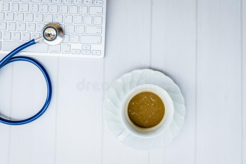 Τοπ στηθοσκόπιο άποψης στο πληκτρολόγιο με το γραφείο γιατρών έννοιας καφέ (διάστημα αντιγράφων στο δικαίωμα) στοκ εικόνα