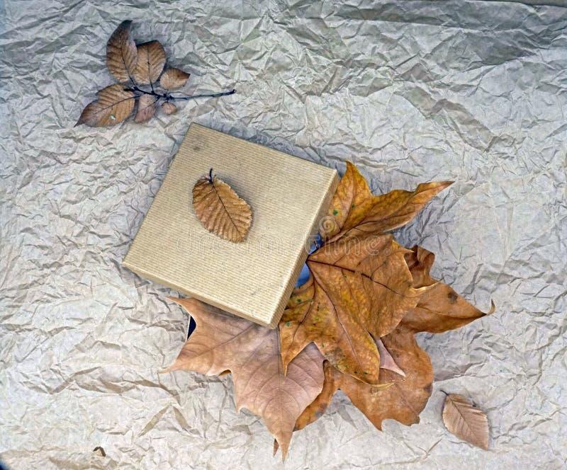 Τοπ σύνθεση άποψης με τα ξηρά φύλλα κιβωτίων και φθινοπώρου δώρων Χρυσή σύνθεση τόνου στο τσαλακωμένο υπόβαθρο εγγράφου να δειπνή στοκ φωτογραφία