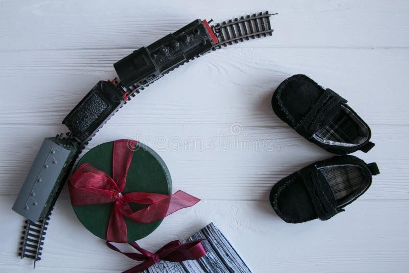 Τοπ σύνολο δώρων στο άσπρο ξύλινο υπόβαθρο , Παιχνίδια, παπούτσια μωρών, τραίνο παιχνιδιών, μούρα που οργανώνονται με το διάστημα στοκ εικόνες