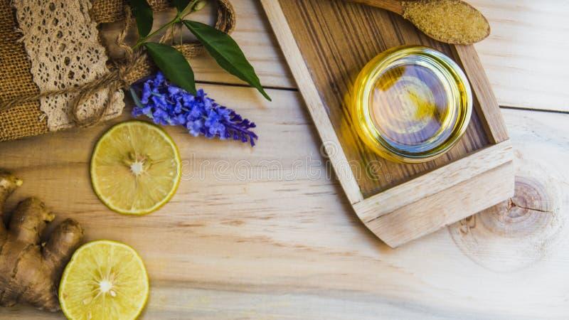 Τοπ τσάι μελιού λεμονιών άποψης που αναμιγνύεται με την πιπερόριζα σε ένα σαφές γυαλί, με ένα κουτάλι και μια καφετιά τσάντα ζάχα στοκ εικόνα με δικαίωμα ελεύθερης χρήσης