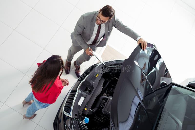 Τοπ φωτογραφία άποψης του νέων αρσενικών συμβούλου και των αγοραστών που υπογράφουν τη σύμβαση για το νέο αυτοκίνητο στοκ εικόνα με δικαίωμα ελεύθερης χρήσης