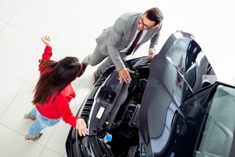 Τοπ φωτογραφία άποψης του νέων αρσενικών συμβούλου και των αγοραστών που υπογράφουν τη σύμβαση για το νέο αυτοκίνητο στοκ φωτογραφίες