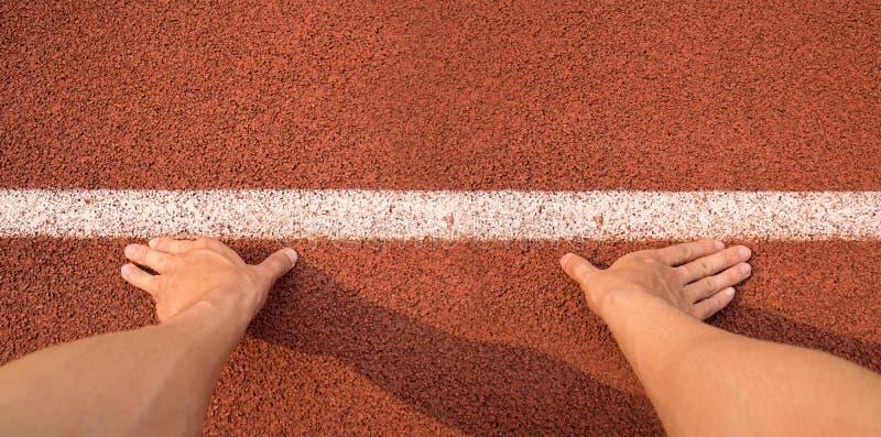 Τοπ χέρια αφής άποψης στην έναρξη γραμμών για το τρέξιμο στη διαδρομή αθλητισμού στοκ εικόνες με δικαίωμα ελεύθερης χρήσης