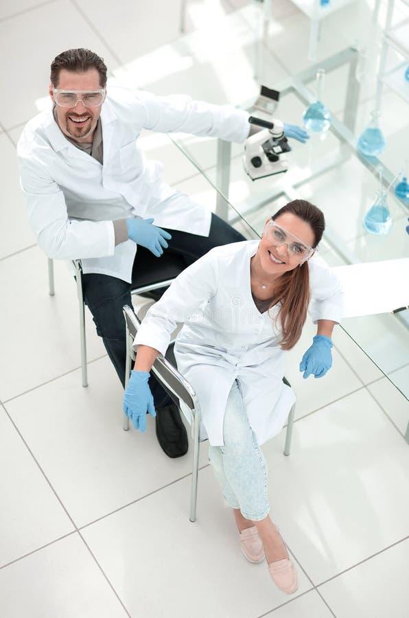 Τοπ όψη δύο χαμογελώντας βοηθοί εργαστηρίων που εξετάζουν τη κάμερα στοκ εικόνα