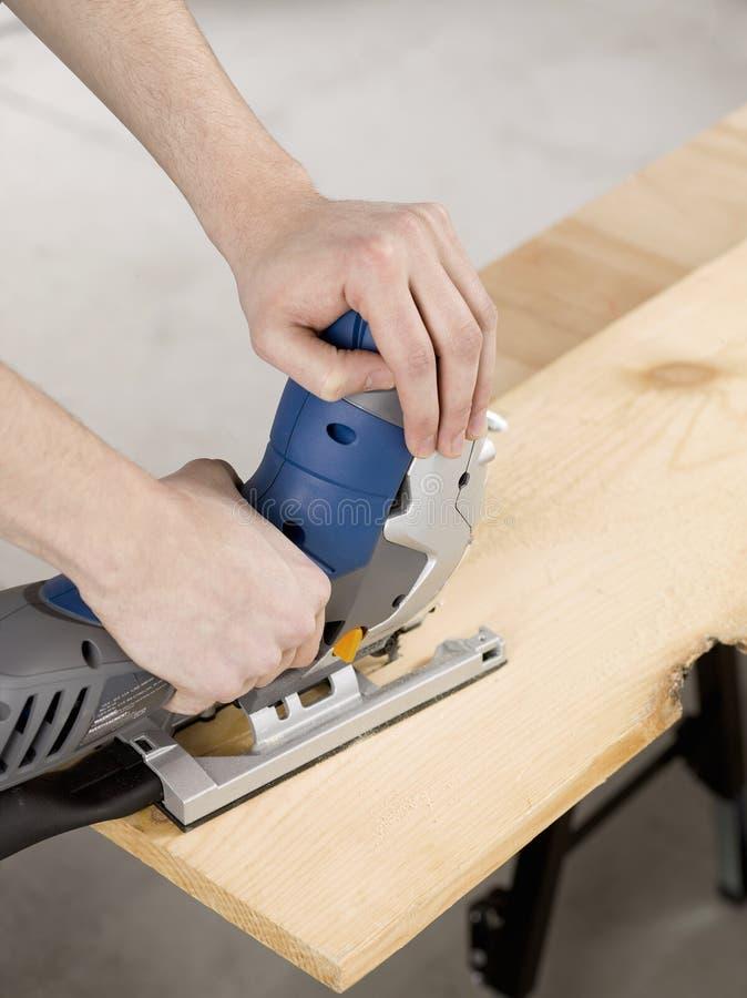 Τορνευτικό πριόνι και κοπή ένα κομμάτι του ξύλου στοκ φωτογραφίες με δικαίωμα ελεύθερης χρήσης