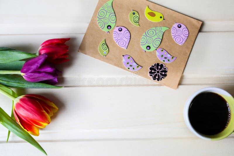 Τουλίπες στο ξύλινο υπόβαθρο με το φλιτζάνι του καφέ Κάρτα πρόσκλησης για την ημέρα της μητέρας ή την ημέρα των διεθνών γυναικών  στοκ φωτογραφίες