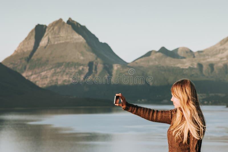 Τουρίστας γυναικών που παίρνει selfie από τα υπαίθριες βουνά και τη θάλασσα ηλιοβασιλέματος της Νορβηγίας διακοπών περιπέτειας έν στοκ εικόνες