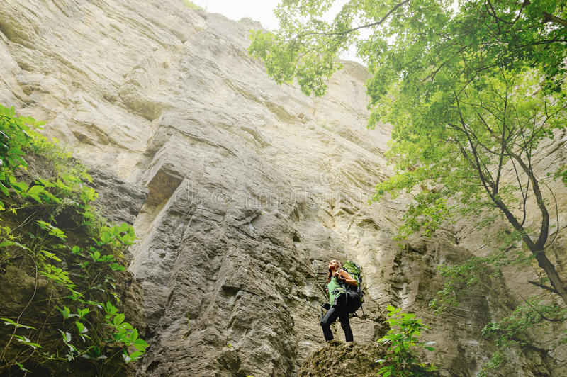 Τουρίστας κοριτσιών με ένα σακίδιο πλάτης που πηγαίνει στο βουνό στοκ εικόνες