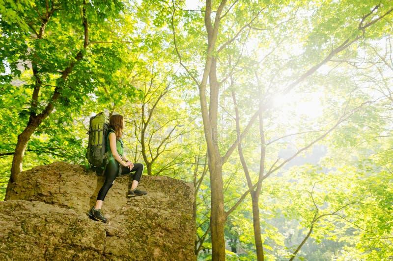 Τουρίστας κοριτσιών με ένα σακίδιο πλάτης που πηγαίνει στο βουνό στοκ φωτογραφίες