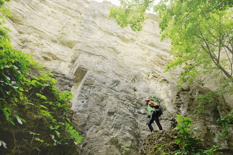 Τουρίστας κοριτσιών με ένα σακίδιο πλάτης που πηγαίνει στο βουνό στοκ εικόνα