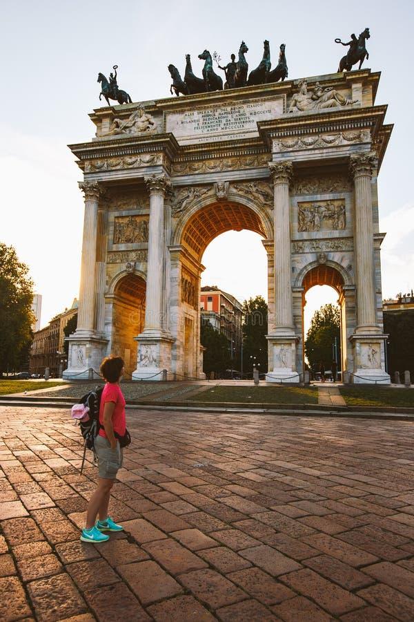 Τουρίστας κοριτσιών που κοιτάζει atArch της ειρήνης στο πάρκο Sempione, Μιλάνο, Λομβαρδία, Ιταλία Arco aka Porta Sempione ρυθμών  στοκ φωτογραφία με δικαίωμα ελεύθερης χρήσης