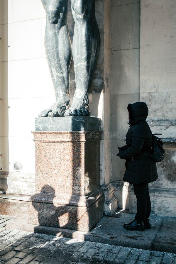 Τουρίστας κοριτσιών στα μαρμάρινα αγάλματα του ανώτατου ορίου λαβής Atlant ` s του νέου ερημητηρίου, Αγία Πετρούπολη, Ρωσία στοκ εικόνες