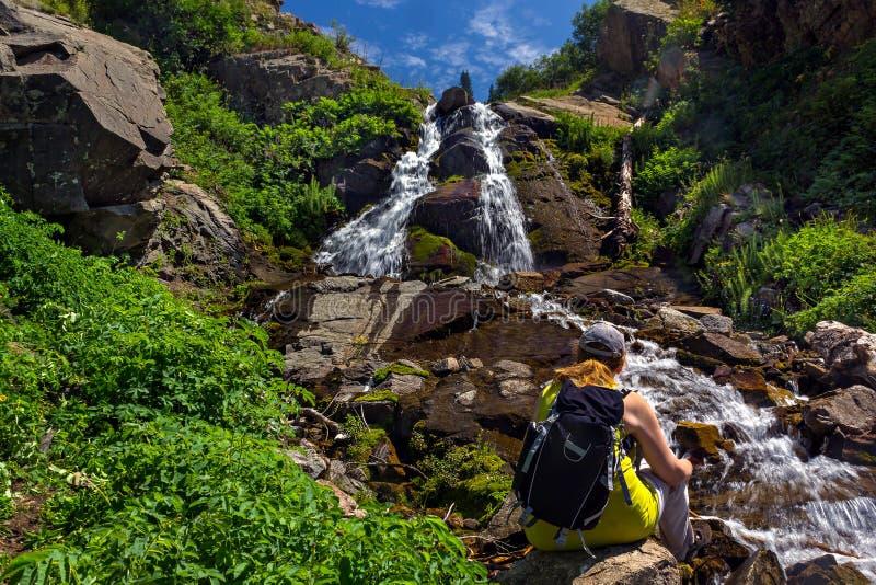 Τουρίστας με μια συνεδρίαση σακιδίων πλάτης από έναν καταρράκτη στα βουνά στοκ φωτογραφίες με δικαίωμα ελεύθερης χρήσης