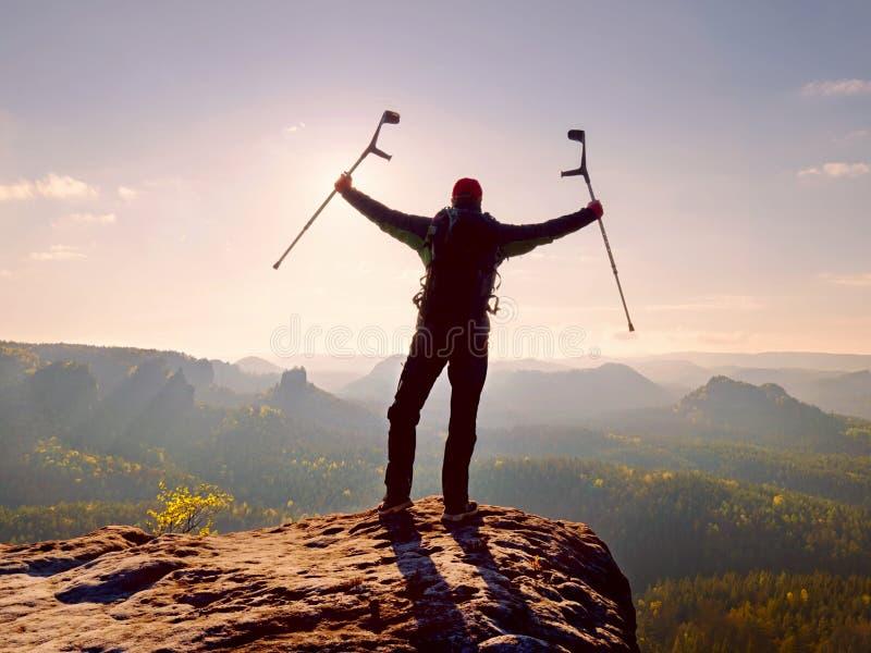 Τουρίστας με το δεκανίκι αντιβράχιων επάνω από το κεφάλι στο ίχνος Βλαμμένη πραγματοποιημένη οδοιπόρος αιχμή βουνών στοκ φωτογραφίες με δικαίωμα ελεύθερης χρήσης