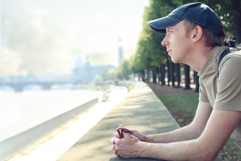 Τουρίστας που απολαμβάνει μια θέα πόλεων από την αποβάθρα, τη λήψη ενός σπασίματος και τη χαλάρωση στοκ φωτογραφία με δικαίωμα ελεύθερης χρήσης