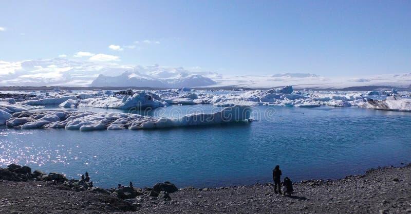 Τουρίστας που βλέπει τα μπλε παγόβουνα στην μπλε λιμνοθάλασσα στοκ φωτογραφία με δικαίωμα ελεύθερης χρήσης