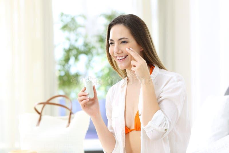 Τουρίστας που εφαρμόζει sunscreen την προστασία σε ένα δωμάτιο ξενοδοχείου στοκ φωτογραφία με δικαίωμα ελεύθερης χρήσης