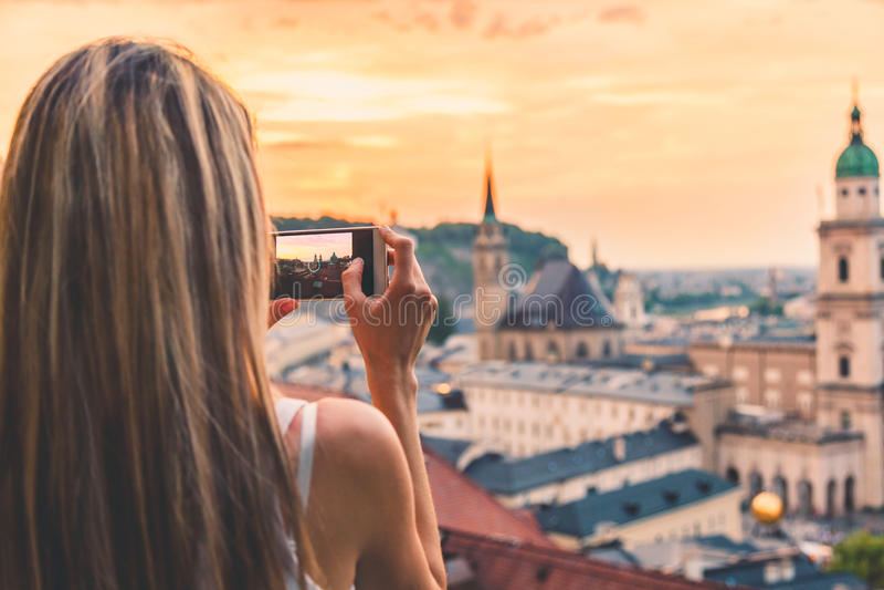 Τουρίστας που παίρνει μια φωτογραφία του όμορφου ηλιοβασιλέματος στο Σάλτζμπουργκ Αυστρία στοκ φωτογραφία