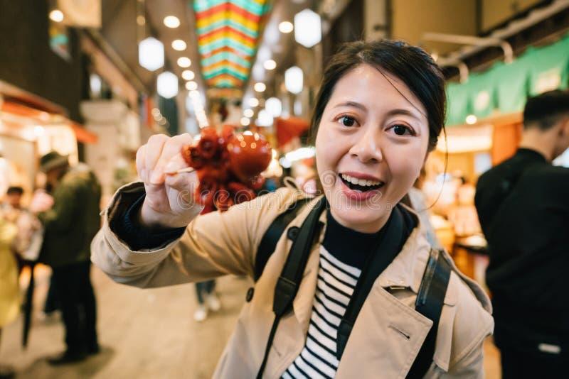 Τουρίστας που παρουσιάζει στους Ιάπωνες λίγο χταπόδι στοκ φωτογραφία