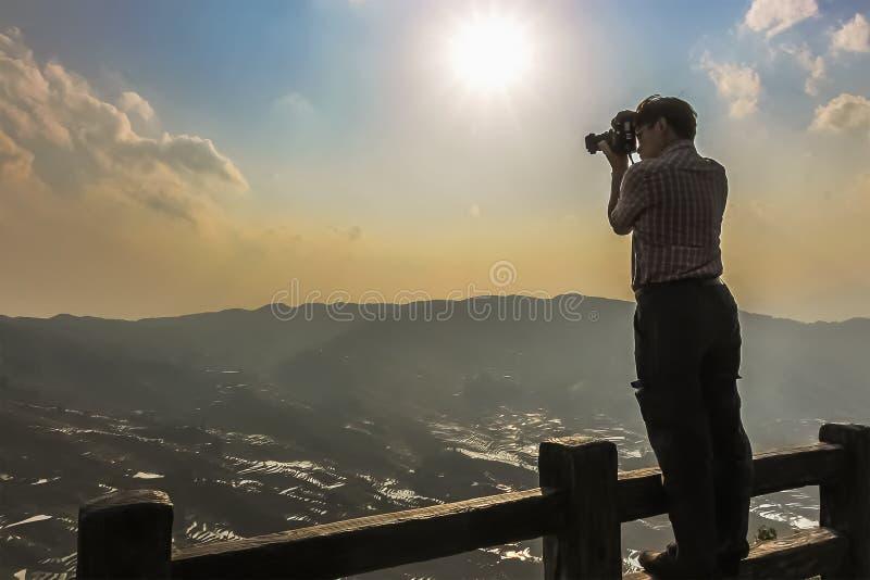 Τουρίστας που στέκεται σε ένα ανώτερο κιγκλίδωμα φρακτών που παίρνει μια φωτογραφία των πεζουλιών ρυζιού σε Bada Yuanyang στοκ φωτογραφία με δικαίωμα ελεύθερης χρήσης