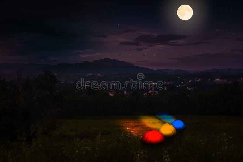 Τουρίστας που στρατοπεδεύει κοντά στο δάσος στη νύχτα Φωτισμένη σκηνή κάτω από το όμορφο σύνολο νυχτερινού ουρανού των αστεριών κ στοκ φωτογραφία με δικαίωμα ελεύθερης χρήσης