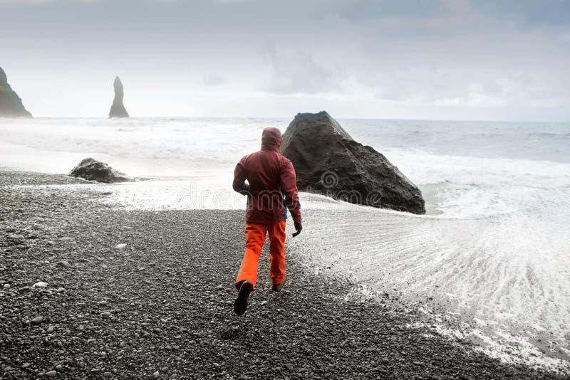 Τουρίστας τύπων που τρέχει στην παραλία στην Ισλανδία, έννοια ελευθερίας στοκ εικόνες