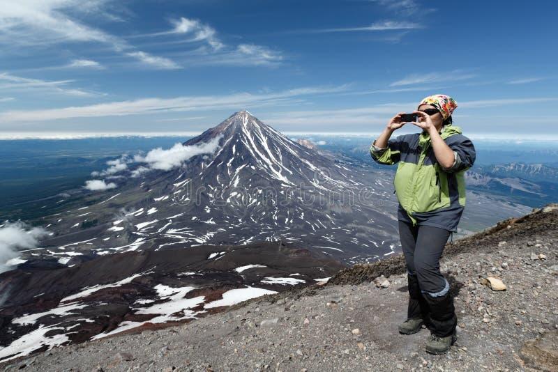 Τουρίστες γυναικών που στέκονται στην άκρη του ηφαιστείου κρατήρων και φωτογραφισμένος στο smartphone στοκ φωτογραφία