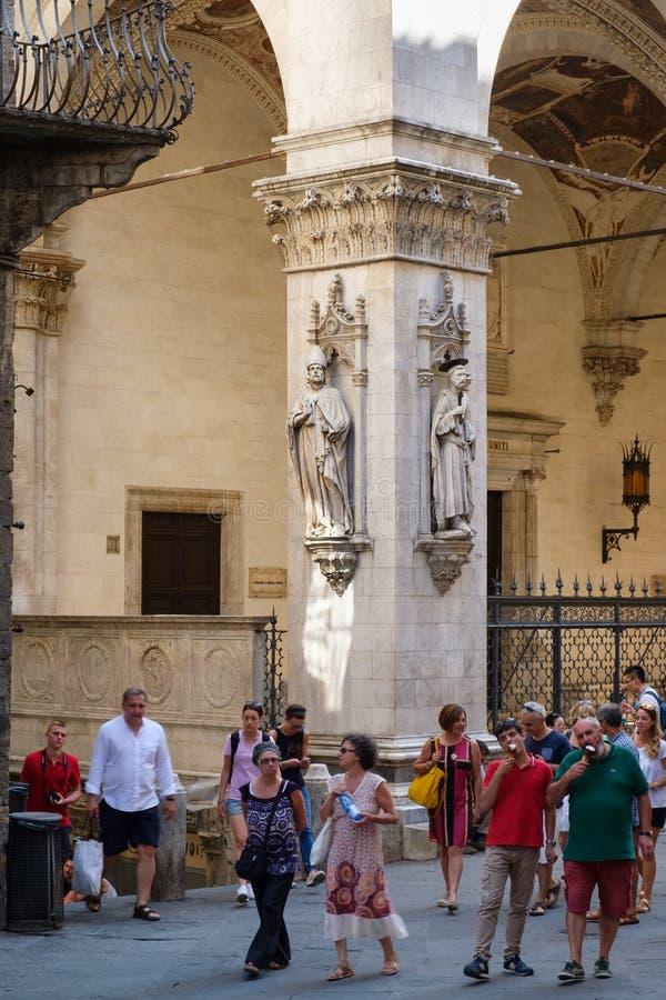 Τουρίστες δίπλα σε ένα παλαιό κτήριο στη μεσαιωνική πόλη της Σιένα, στοκ φωτογραφία με δικαίωμα ελεύθερης χρήσης