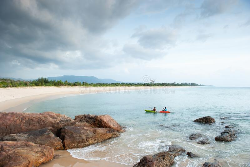 Τουρίστες ζεύγους που στην τροπική θάλασσα Stone, βράχοι, κύματα foregrounds, κυρτός κόλπος, βουνά και νεφελώδη υπόβαθρα Tai Muan στοκ φωτογραφίες με δικαίωμα ελεύθερης χρήσης