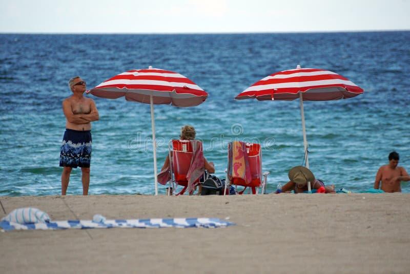 Τουρίστες κάτω από τις κόκκινες και άσπρες ριγωτές ομπρέλες παραλιών στην παραλία Dania στοκ φωτογραφίες