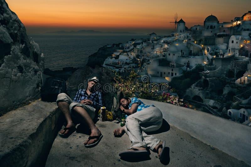 Τουρίστες με τα σακίδια πλάτης που κοιμούνται στο Oia χωριό στοκ εικόνες