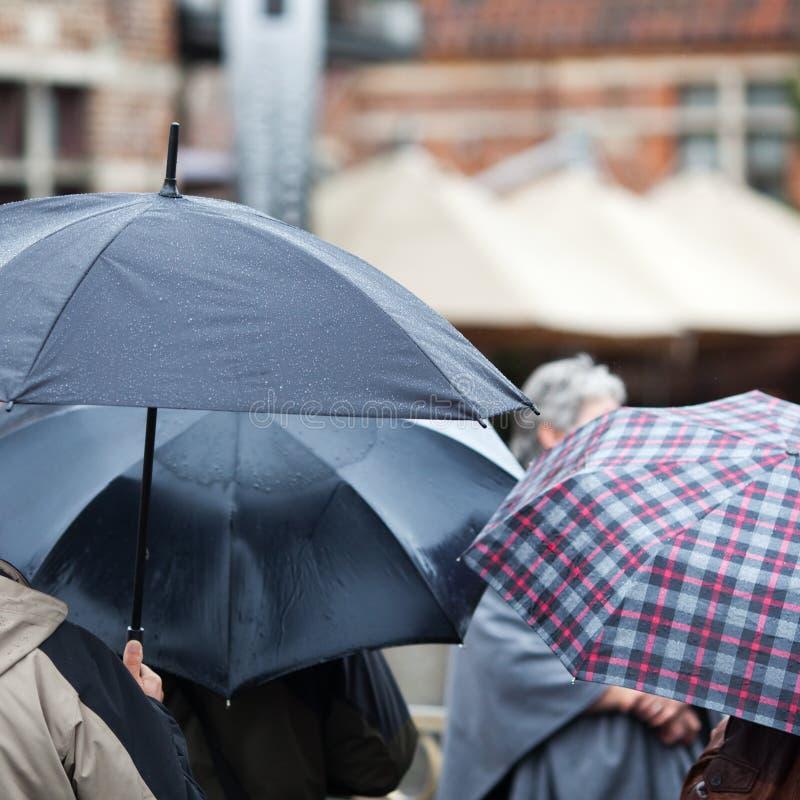 Τουρίστες με τις ομπρέλες που στέκονται στη βροχή στοκ εικόνες