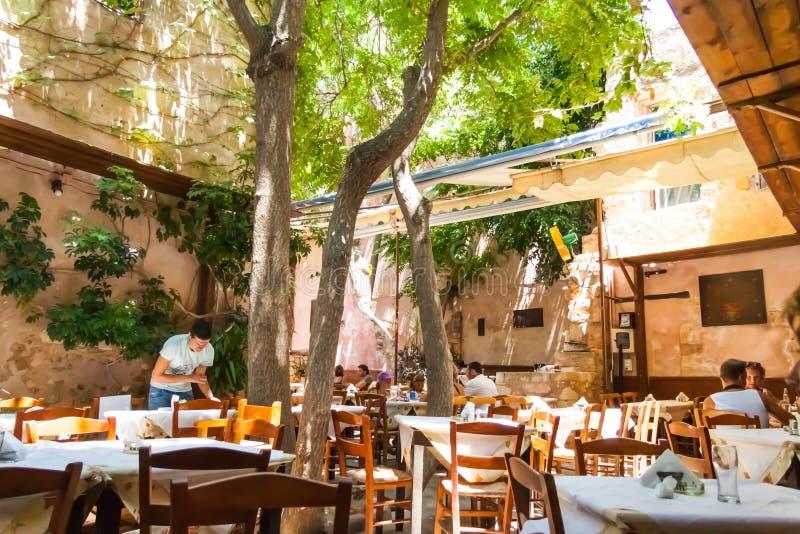 Τουρίστες που έχουν το μεσημεριανό γεύμα σε ένα εστιατόριο στην παλαιά πόλη Chania στοκ εικόνα