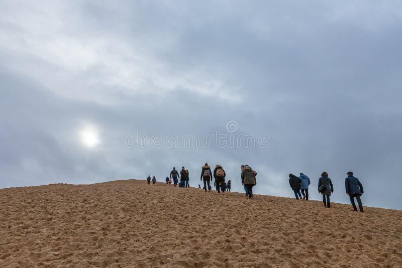 Τουρίστες που αναρριχούνται στο Pilat Dune Dune du Pilat κατά τη διάρκεια ενός νεφελώδους απογεύματος στοκ φωτογραφία με δικαίωμα ελεύθερης χρήσης