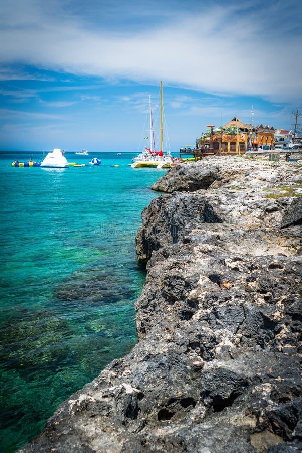 Τουρίστες που απολαμβάνουν τις δραστηριότητες τραμπολίνων νερού την ηλιόλουστη θερινή ημέρα στο τροπικό νησί Καραϊβικής στοκ εικόνες
