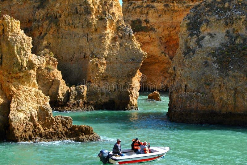 Τουρίστες που απολαμβάνουν τη θέα των θεαματικών σχηματισμών βράχου από μια βάρκα στοκ φωτογραφίες