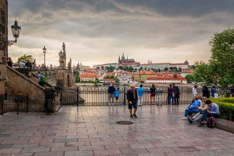 Τουρίστες που εξετάζουν τη γέφυρα και το Κάστρο της Πράγας του Charles στην Πράγα κατά τη διάρκεια του ηλιοβασιλέματος, Δημοκρατί στοκ φωτογραφία