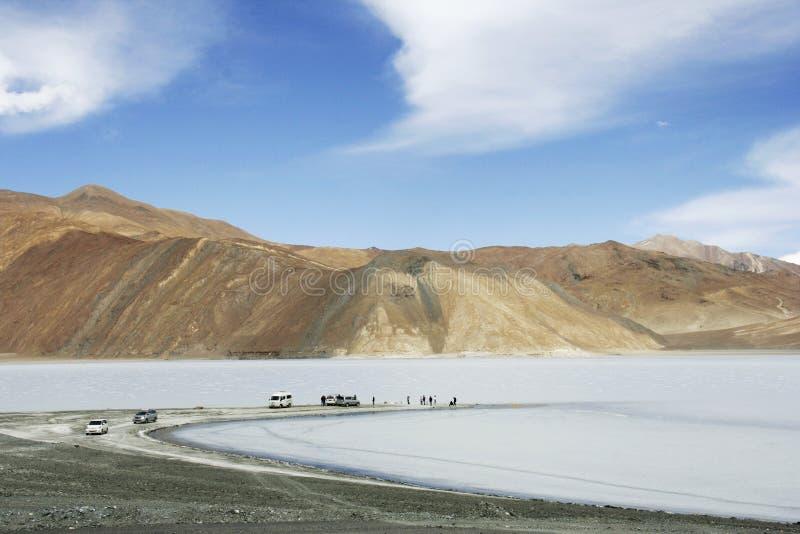 Τουρίστες που επισκέπτονται την παγωμένη λίμνη Pangong με το σαφή μπλε ουρανό στον παλληκάρι στοκ φωτογραφία