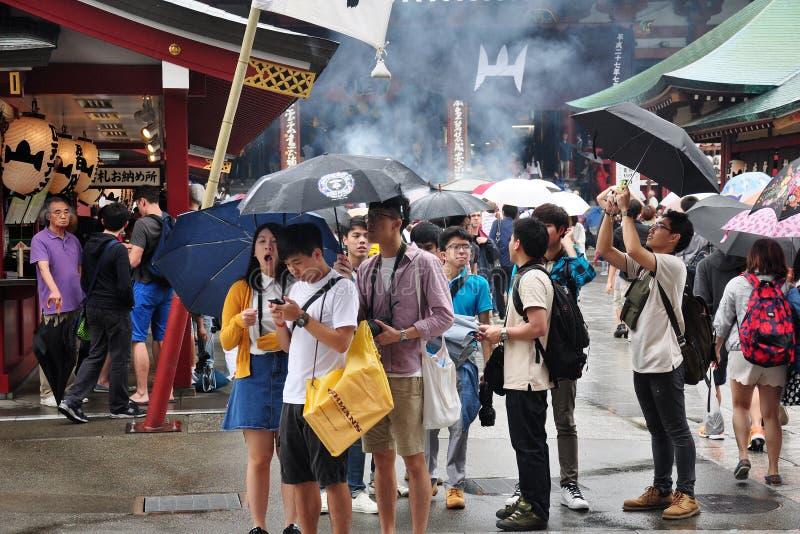 Τουρίστες που κρατούν την ομπρέλα περπατώντας ή πυροβολώντας βρέχοντας για την επίσκεψη στο ναό Sensoji στοκ εικόνα