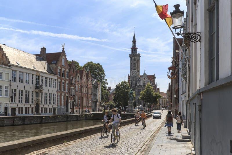 Τουρίστες που οδηγούν τα ποδήλατα στις οδούς της Μπρυζ, Φλαμανδική περιοχή στο Βέλγιο στοκ εικόνα