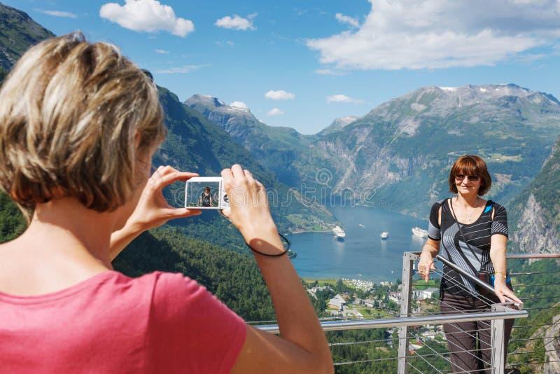Τουρίστες που παίρνουν τη φωτογραφία ενάντια σε Geirangerfjord στοκ φωτογραφία