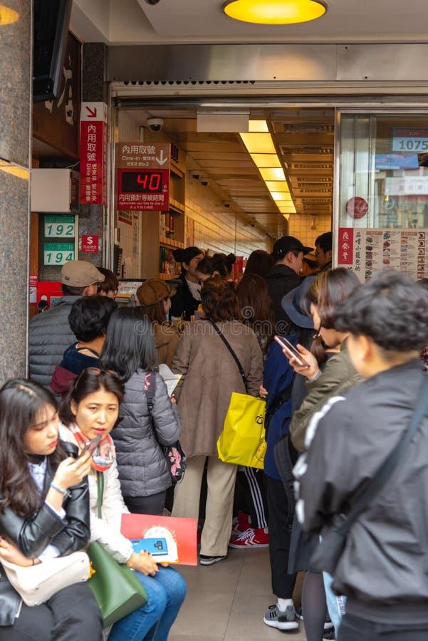 Τουρίστες που περιμένουν στη σειρά στο αρχικό εστιατόριο DIN Tai Fung mainstore στο δρόμο Xinyi Το Michelin απονεμημένο αστέρι Di στοκ εικόνα