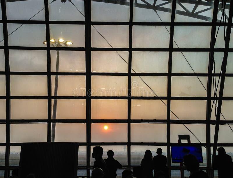 Τουρίστες που περιμένουν την πτήση πρωινού στην πύλη αερολιμένων και αυτοί που κοιτάζουν μέσω του γυαλιού παραθύρων για να δει το στοκ φωτογραφίες