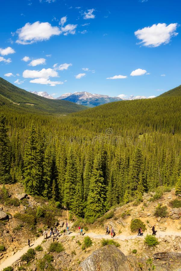 Τουρίστες που περπατούν προς τη λίμνη Moraine στα καναδικά δύσκολα βουνά στοκ φωτογραφίες