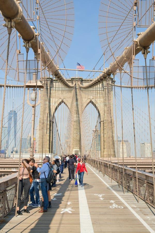 Τουρίστες που περπατούν στη γέφυρα του Μπρούκλιν προς το Μανχάταν σε νέο στοκ φωτογραφίες