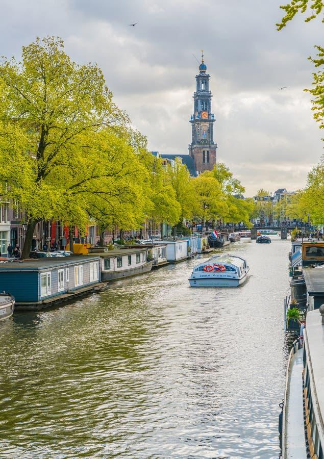 Τουρίστες που πλέουν σε μια βάρκα καναλιών στο Prinsengracht που περνά το Westertoren στοκ φωτογραφία με δικαίωμα ελεύθερης χρήσης