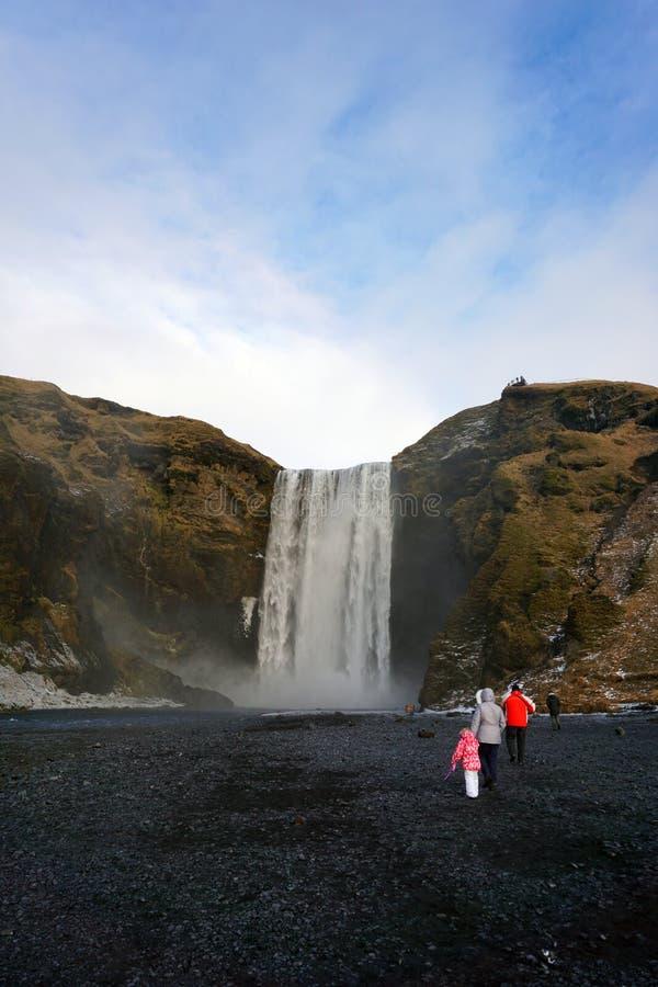 Τουρίστες σε Skogafoss το χειμώνα της Ισλανδίας στοκ φωτογραφίες