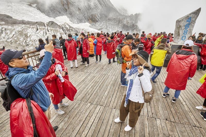 Τουρίστες στην πλατφόρμα εξέτασης βουνών χιονιού δράκων νεφριτών που καλύπτεται με τα σύννεφα στοκ εικόνα