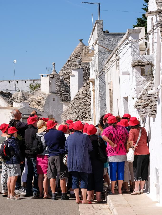 Τουρίστες στην πόλη Puglian Alberobello, που εξετάζει και που φωτογραφίζει τα παραδοσιακά σπίτια trulli ξηρών πετρών που είναι μο στοκ εικόνες με δικαίωμα ελεύθερης χρήσης